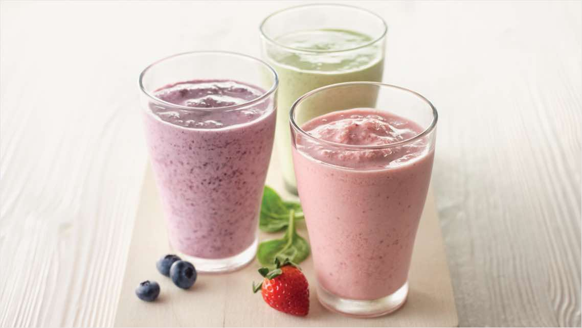 Three colorful protein shakes on the counter.