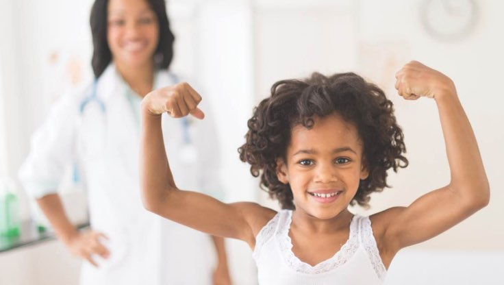 Young girl flexing her muscles with mom in the background.