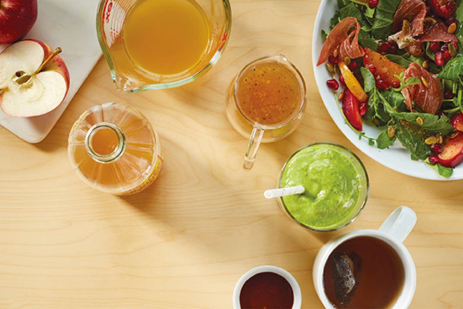 Cups of apple-cider vinegar and green smoothie next to a bowl of salad