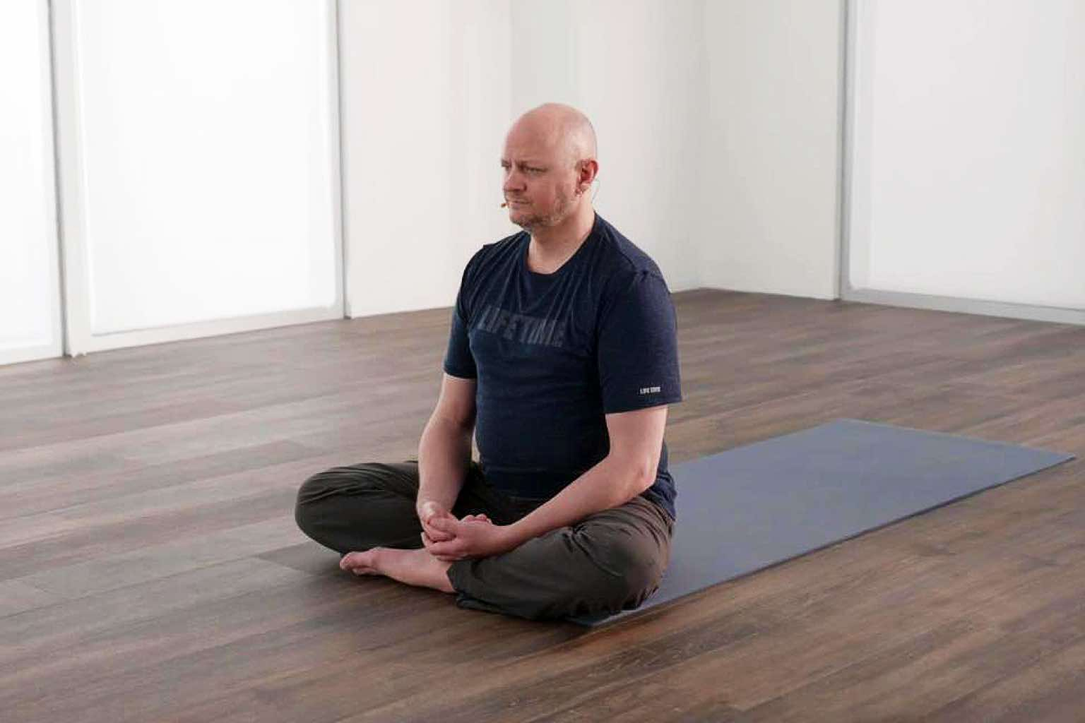 Man sitting in a cross-legged position on a yoga mat