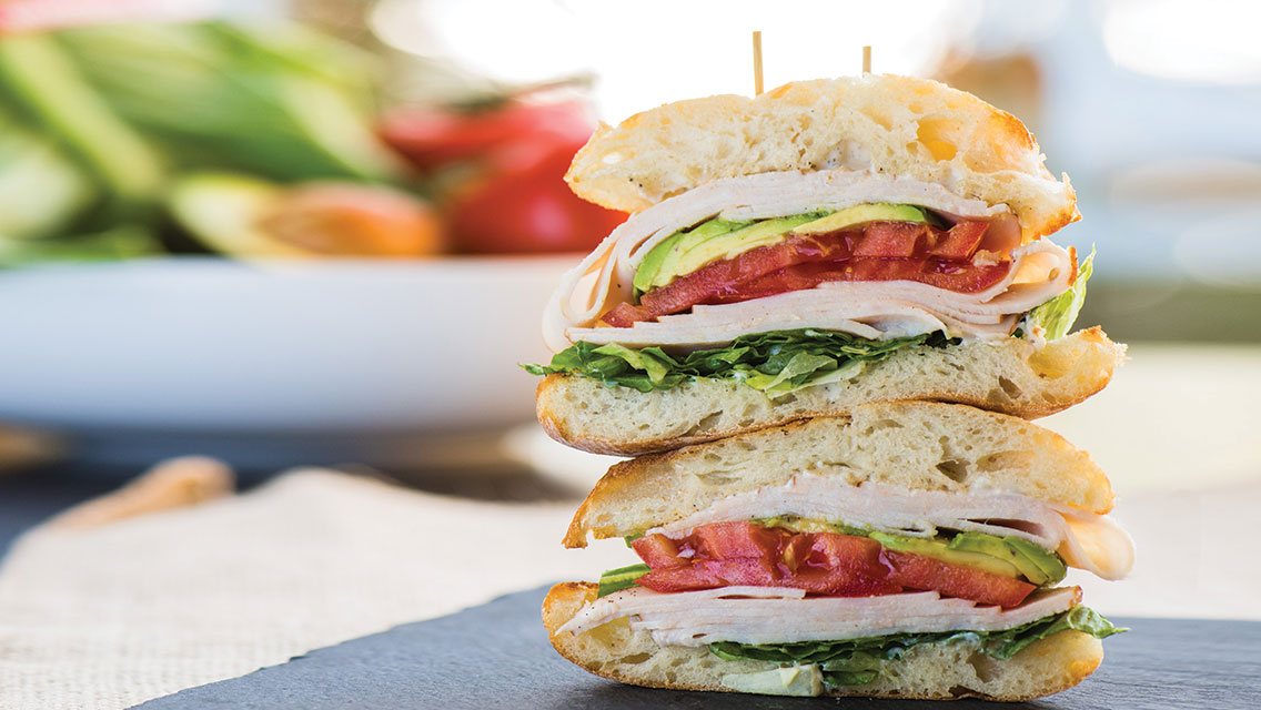 a stacked turkey avocado sandwich with fresh vegetables behind it