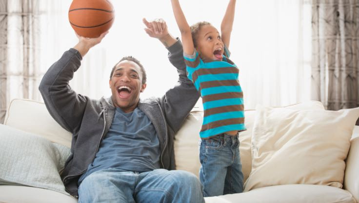 Father and son celebrating on a couch.