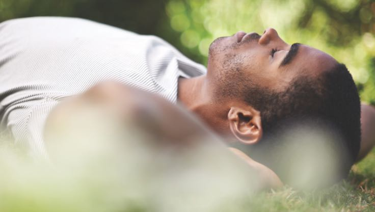 Man relaxing and lying on the grass.