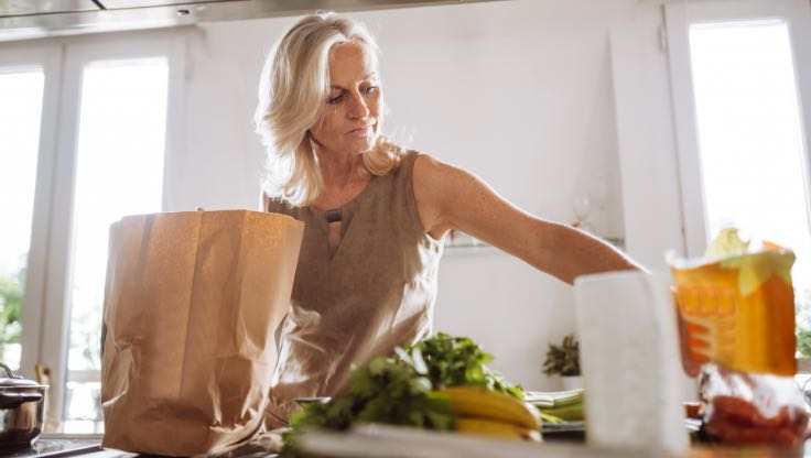 Woman unpacking her groceries at home.