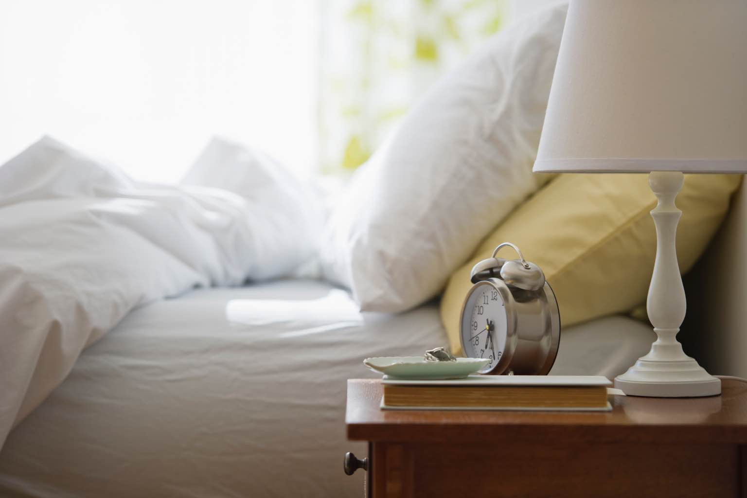 Nightstand with lamp and alarm clock next to a bed