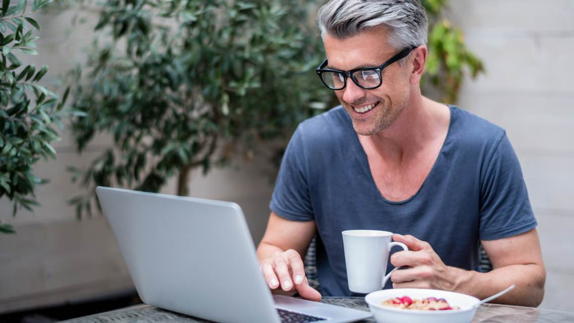 Man sitting at a table with laptop, breakfast plate and coffee cup