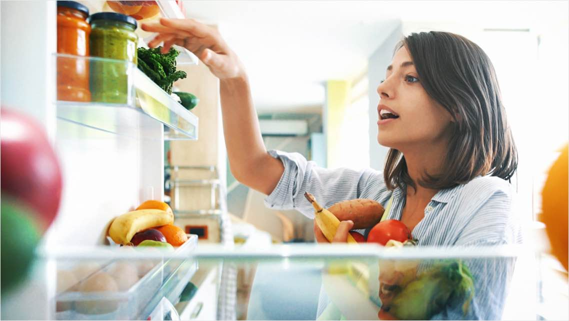 Woman grabbing food out of her refrigerator