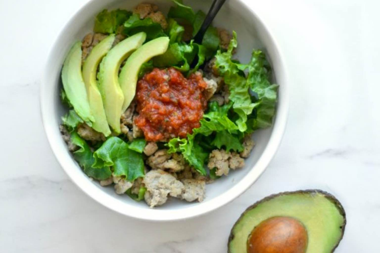 Taco bowl with avocado, salsa, ground meat and lettuce