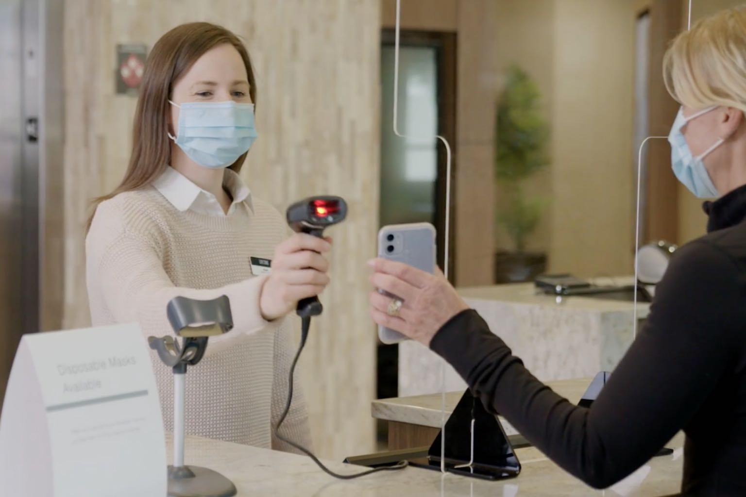a life time employee wearing a mask scans a members phone at the front desk