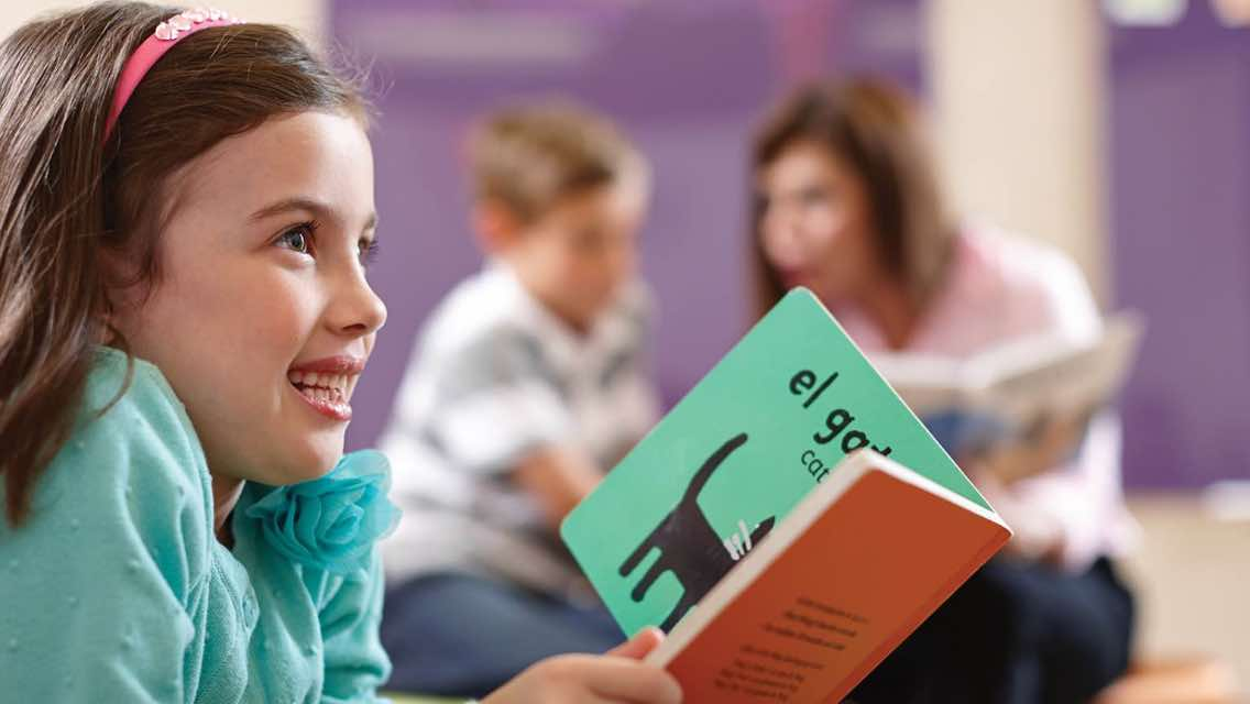 A girl reading a book in Spanish at Life Time distance learning