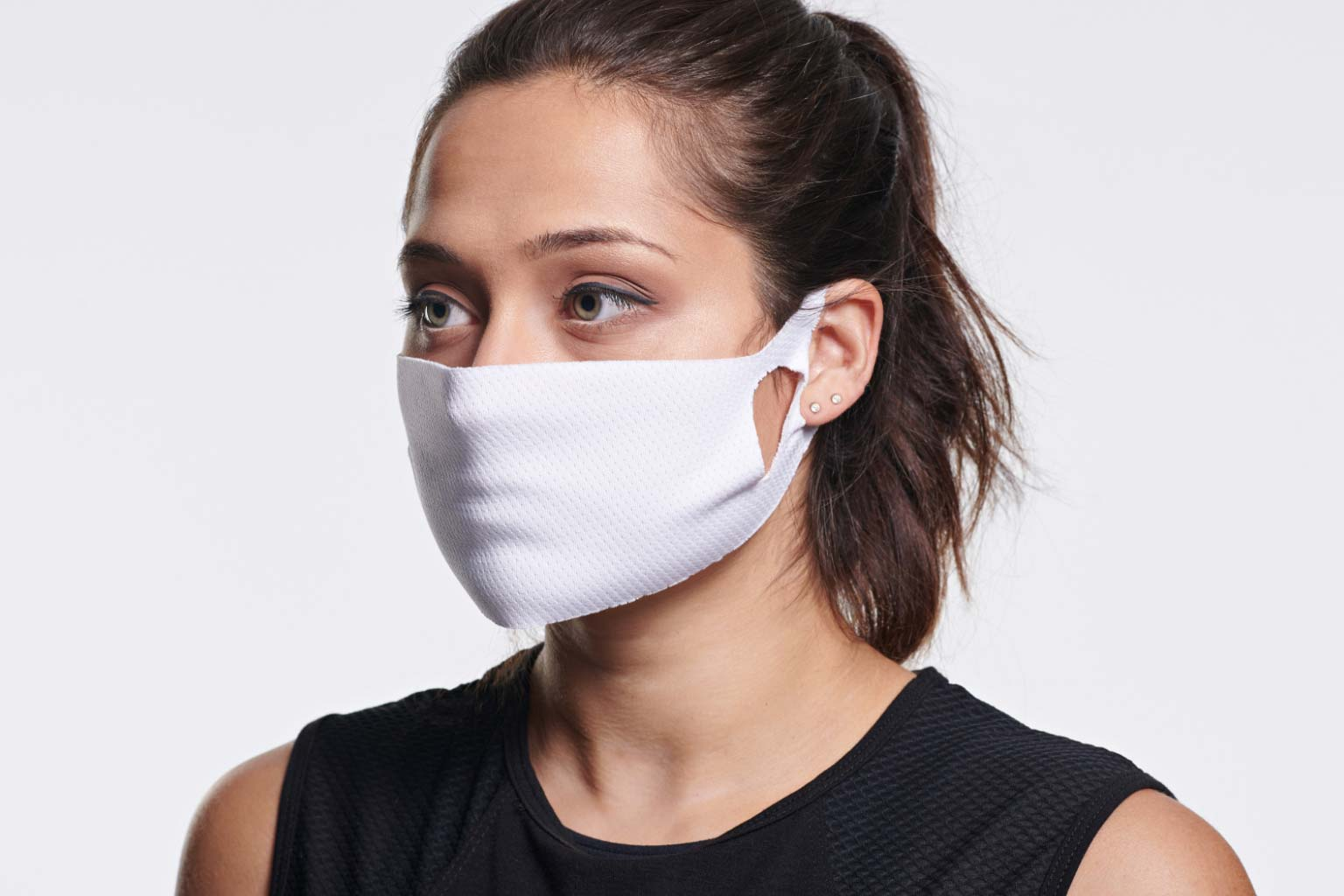 Woman wearing a white athletic comfort mask from Life Time