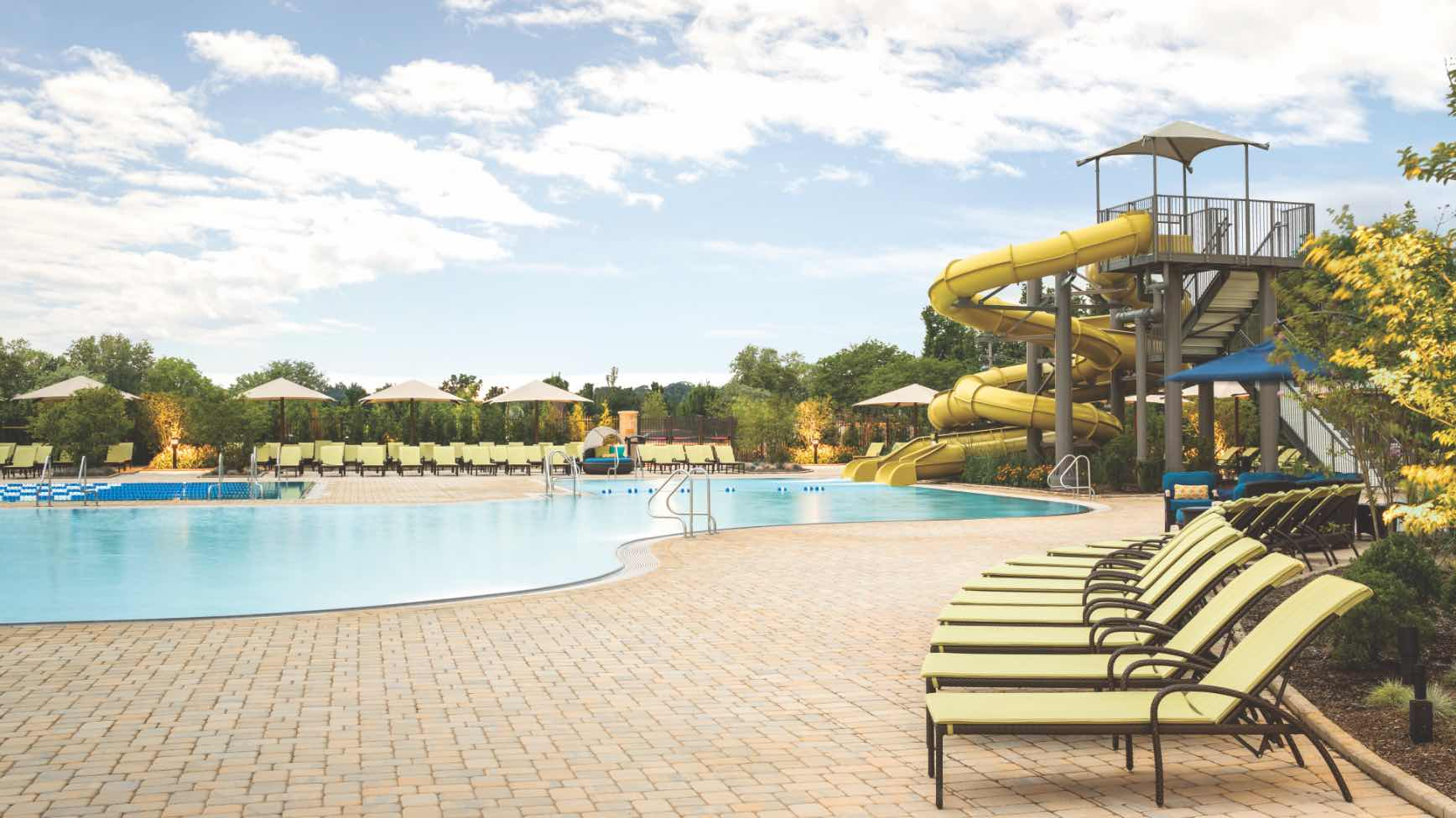 a row of lounge chairs by a leisure pool and water slides.