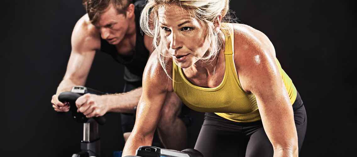 A blonde woman in a yellow tank top sweating in a cycle class