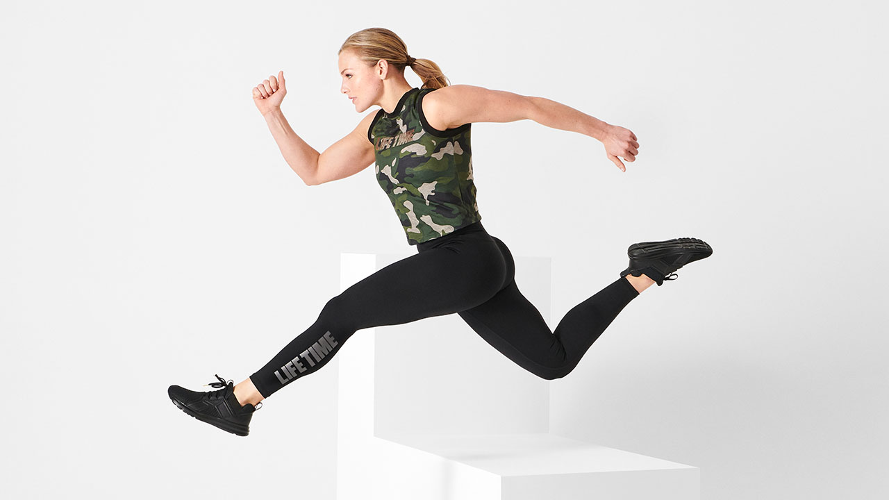 Blonde girl hurdling wearing Life Time apparel