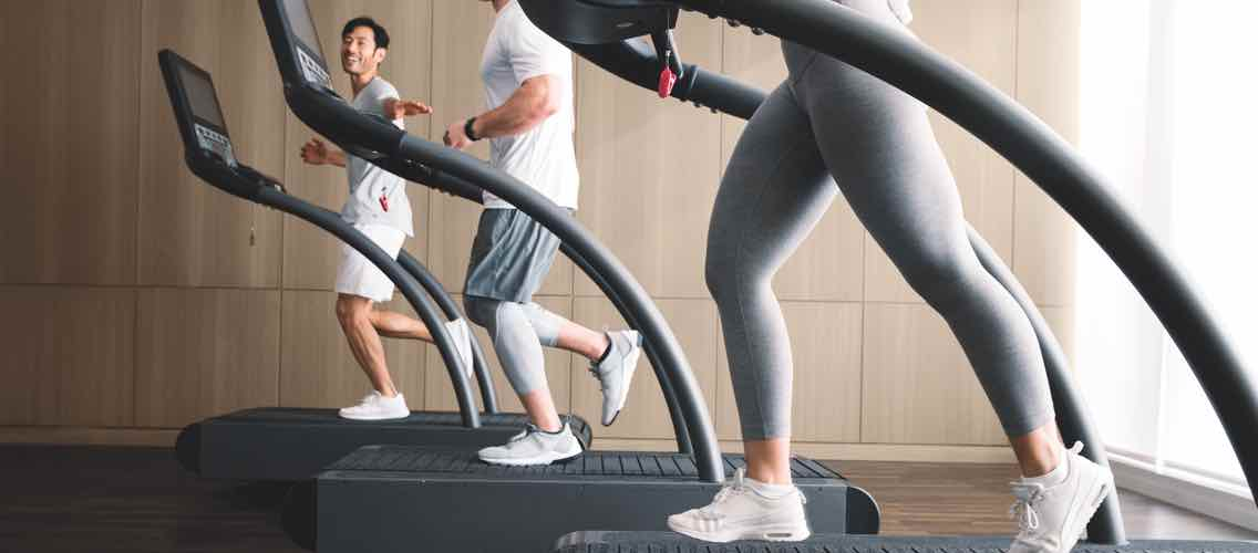 Three people in exercise clothes working out on treadmills
