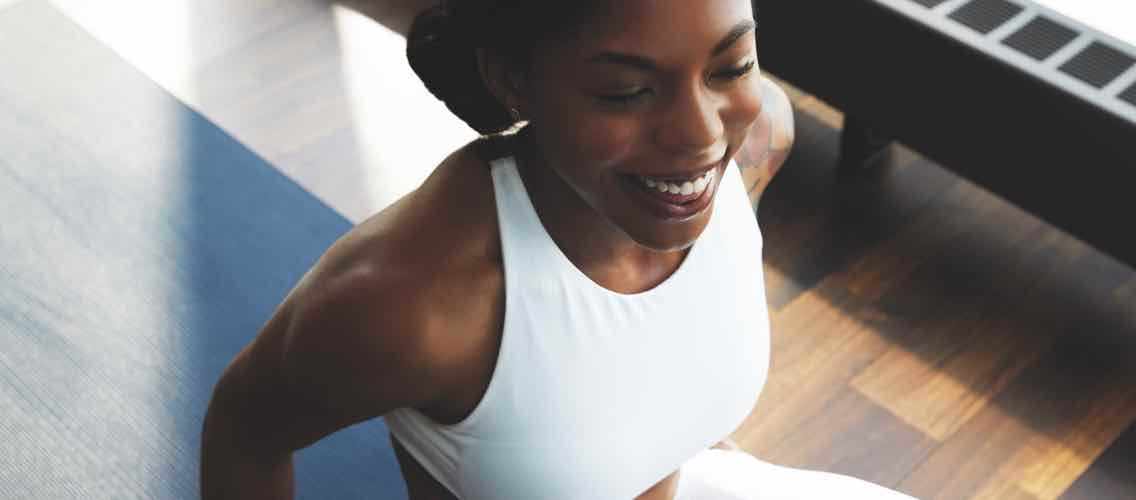 A smiling woman in workout gear sitting on a blue yoga mat
