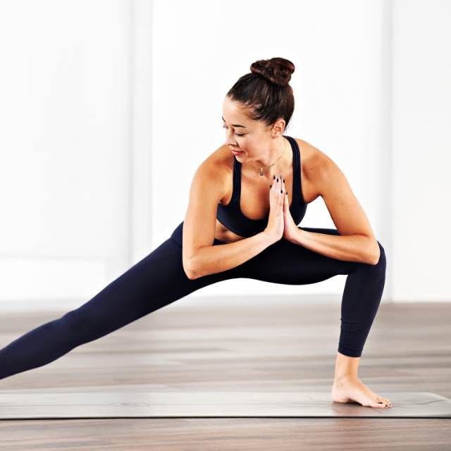 Woman taking a yoga flow class at home with Life Time Classes On Demand