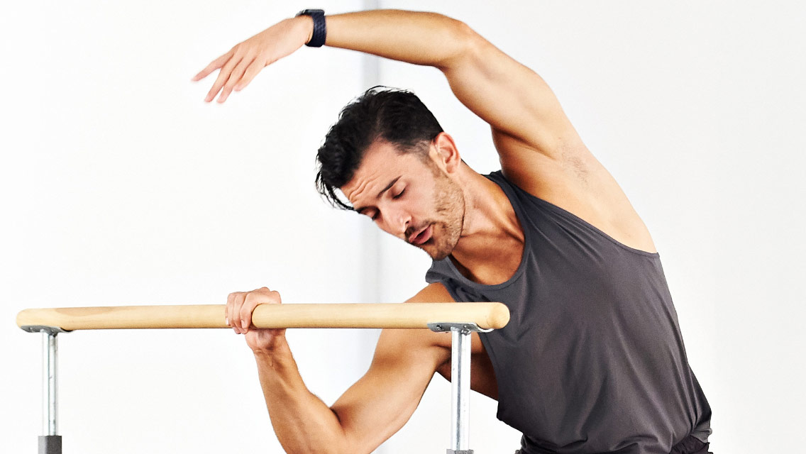 a man performs an overhead side reach while holding a barre