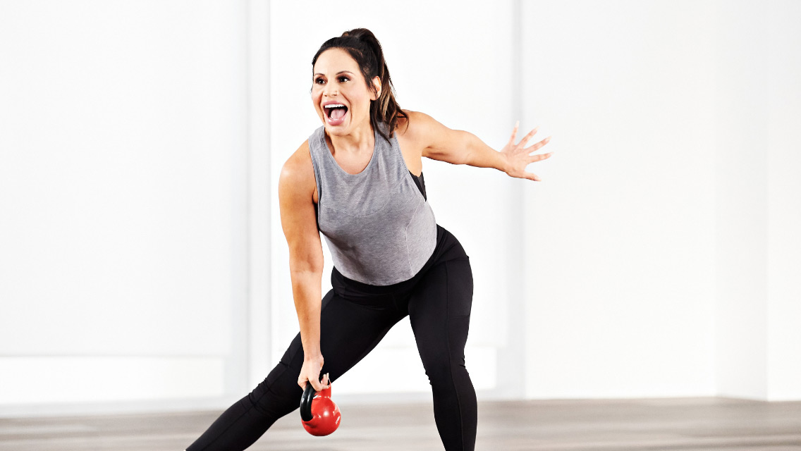 a woman performs a side lunge while holding a kettlebell