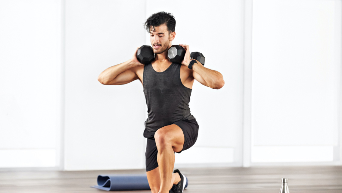 a man performs a lunge with dumbbells