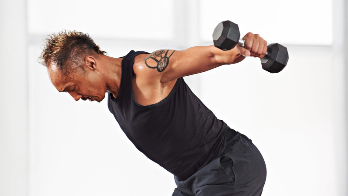 a man uses dumbbells to do a bent over fly