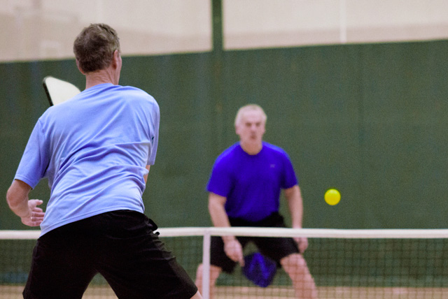 A man hitting a ball over a net to a player who's waiting to return it