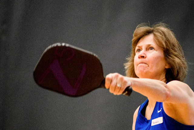 A pickleball player with racquet outstretched, ready to hit the ball