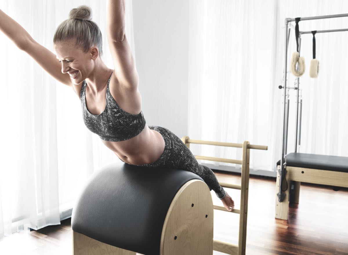 A woman balancing on an exercise ball with arms upraised