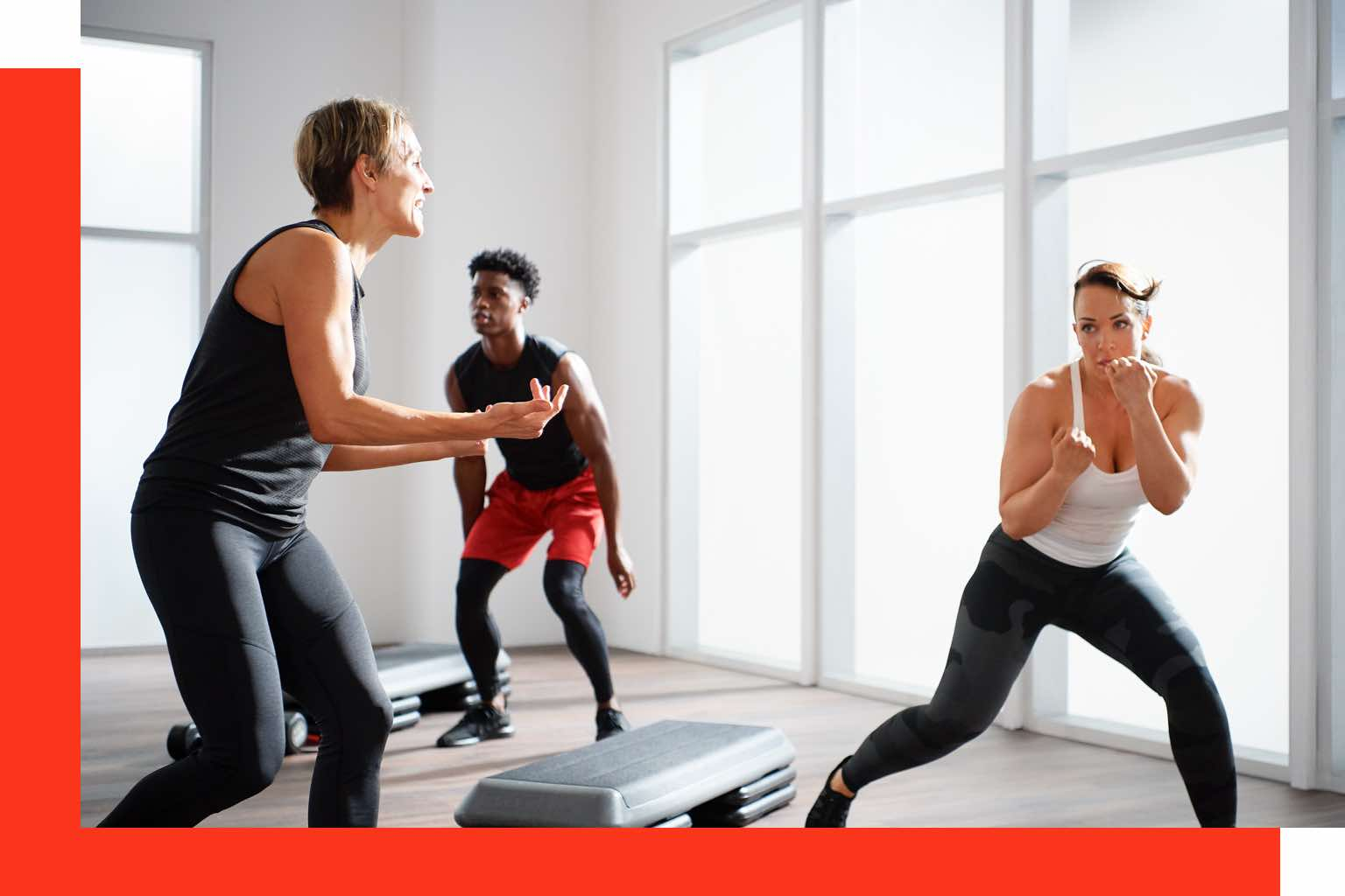 Three people practicing boxing moves in a group fitness class at Life Time