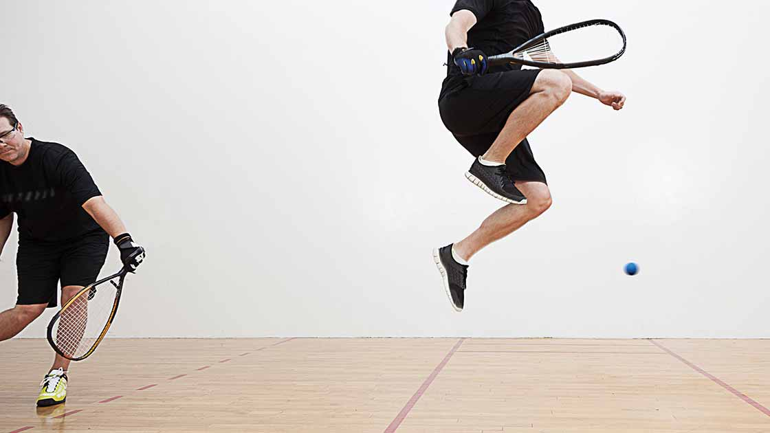 Image of two adults playing racquetball and jumping
