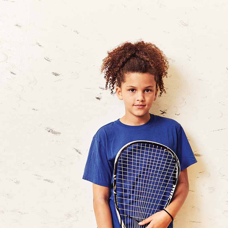 Image of a curly-haired kid holding a racquetball racquet