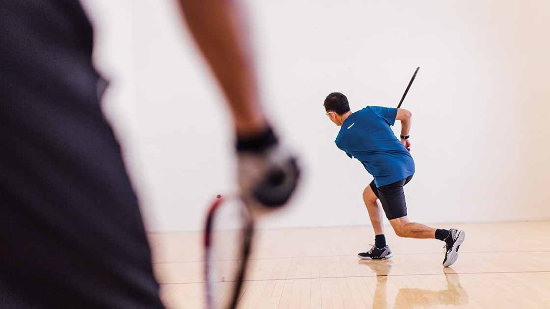 image of two adults playing in a racquetball court