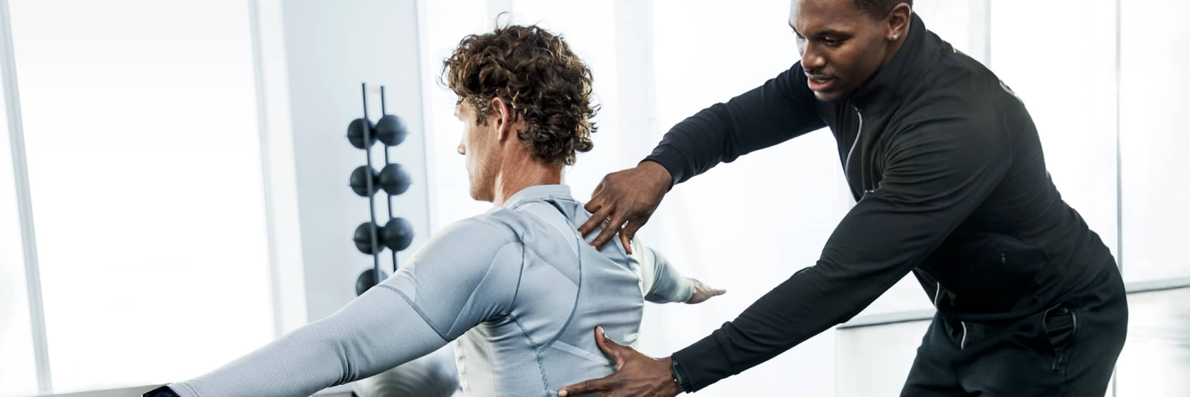 A trainer applies pressure to his client's upper back during a session