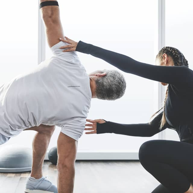 A Life Time trainer helps her client complete a side stretch