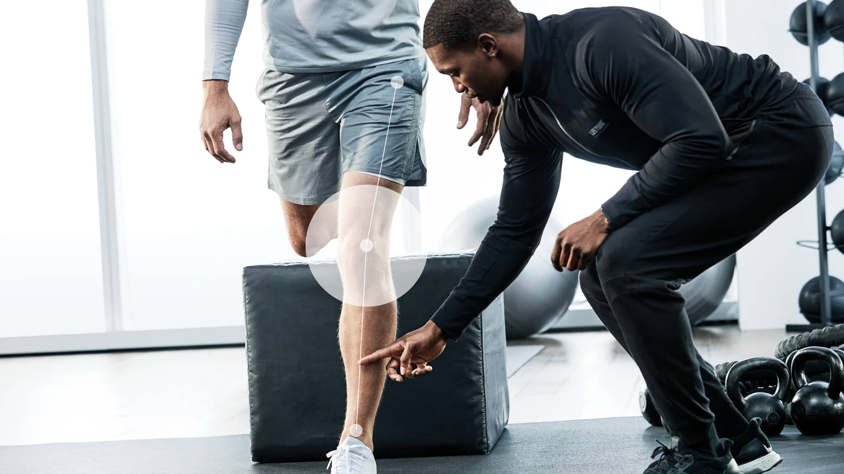 A Life Time trainer helps his client with proper form during an exercise