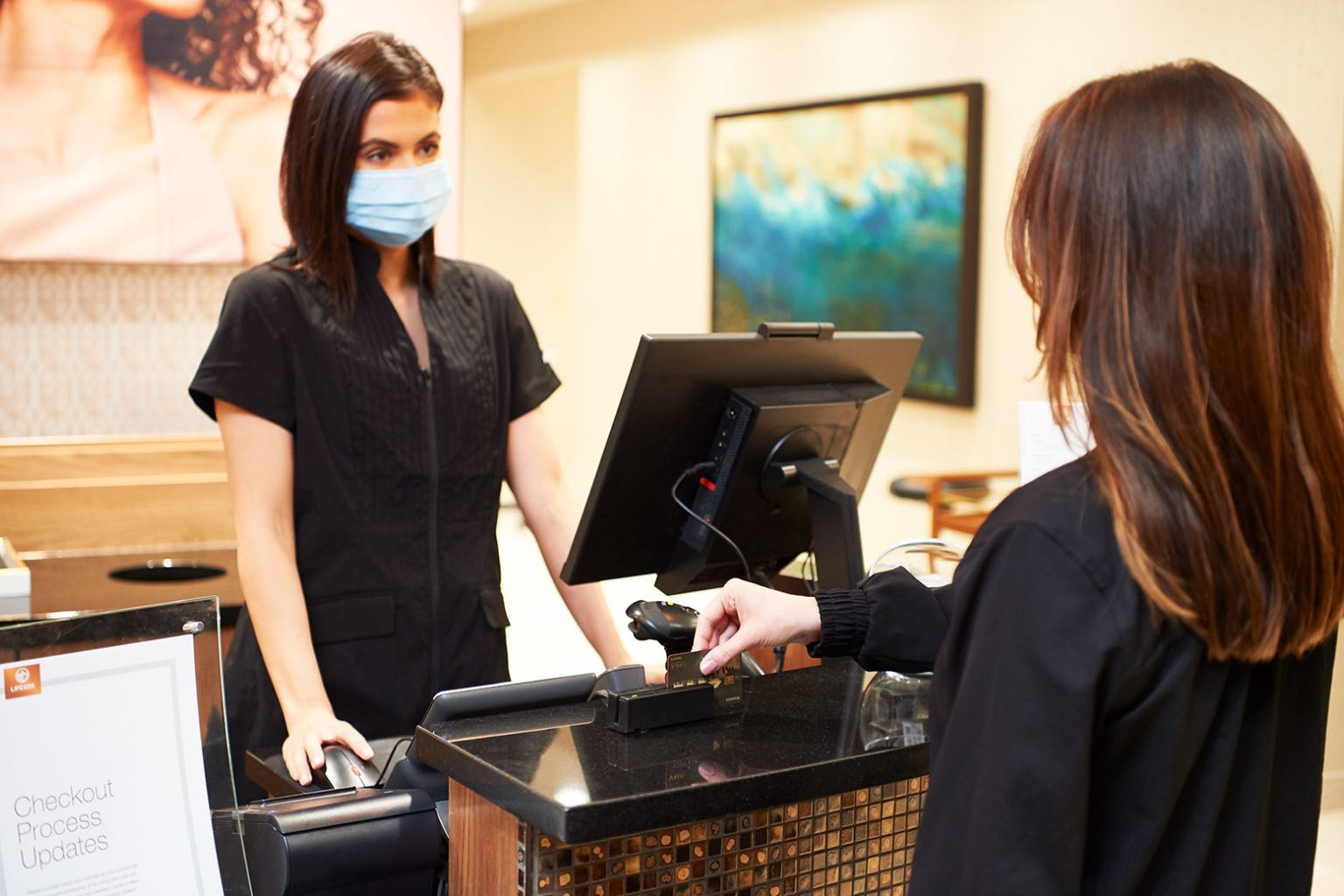 Front desk at a lifespa with a team member wearing a mask.