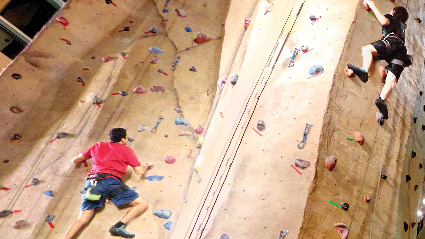 Two people rock climbing on a rockwall at Life Time.