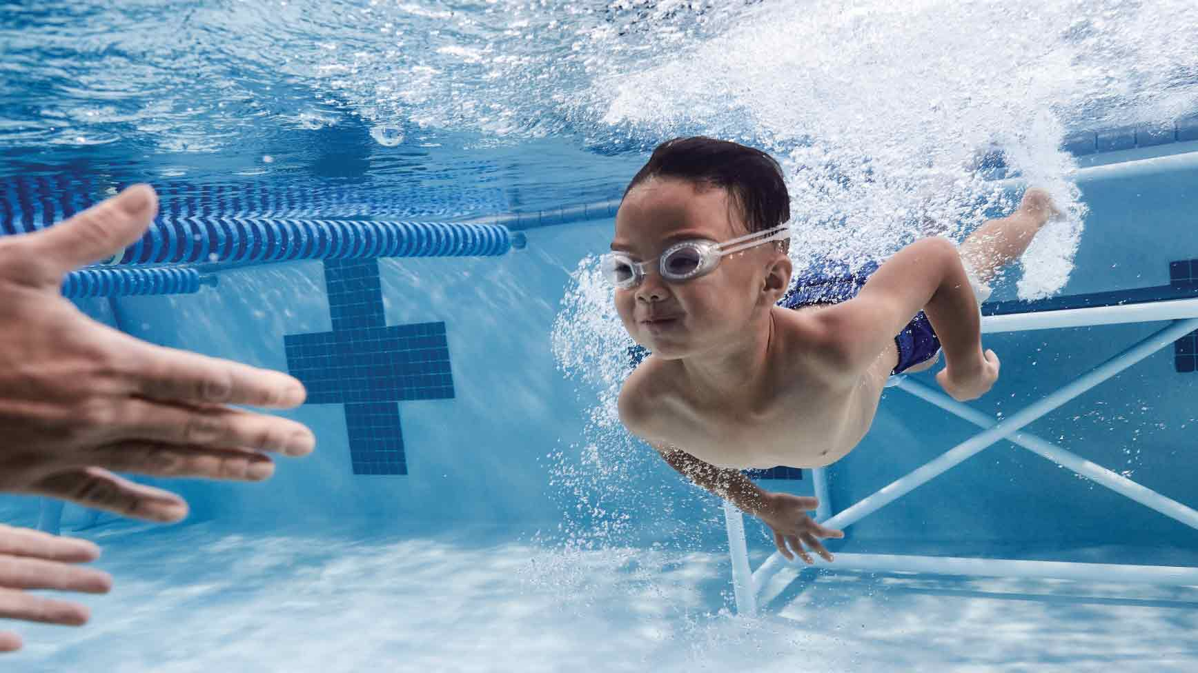 Small boy swimming underwater at a Life Time