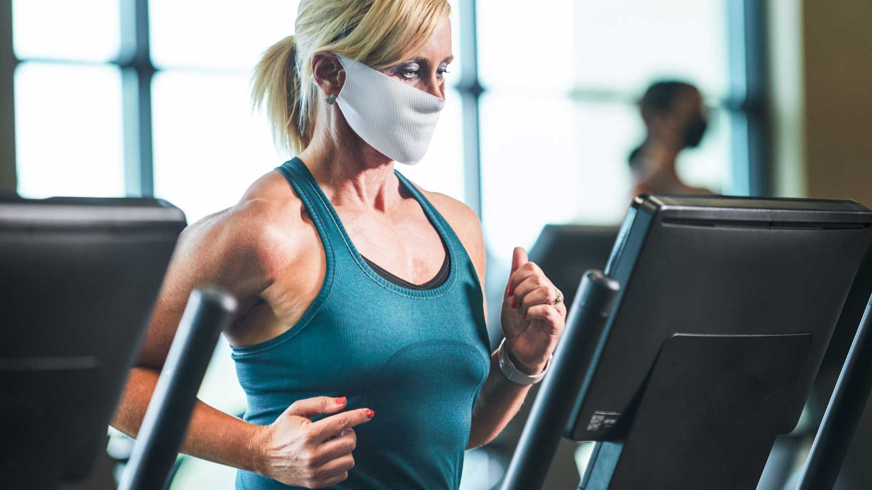 Woman running on a treadmill with a mask.