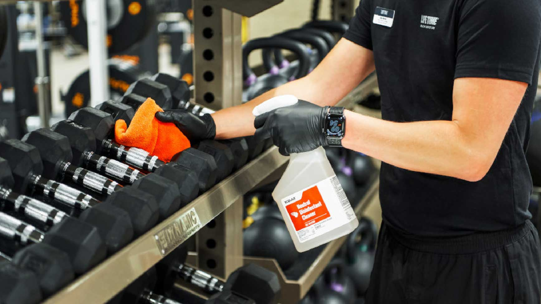 Close up shot of a team member wiping down dumbbells with virus killing disinfectant.