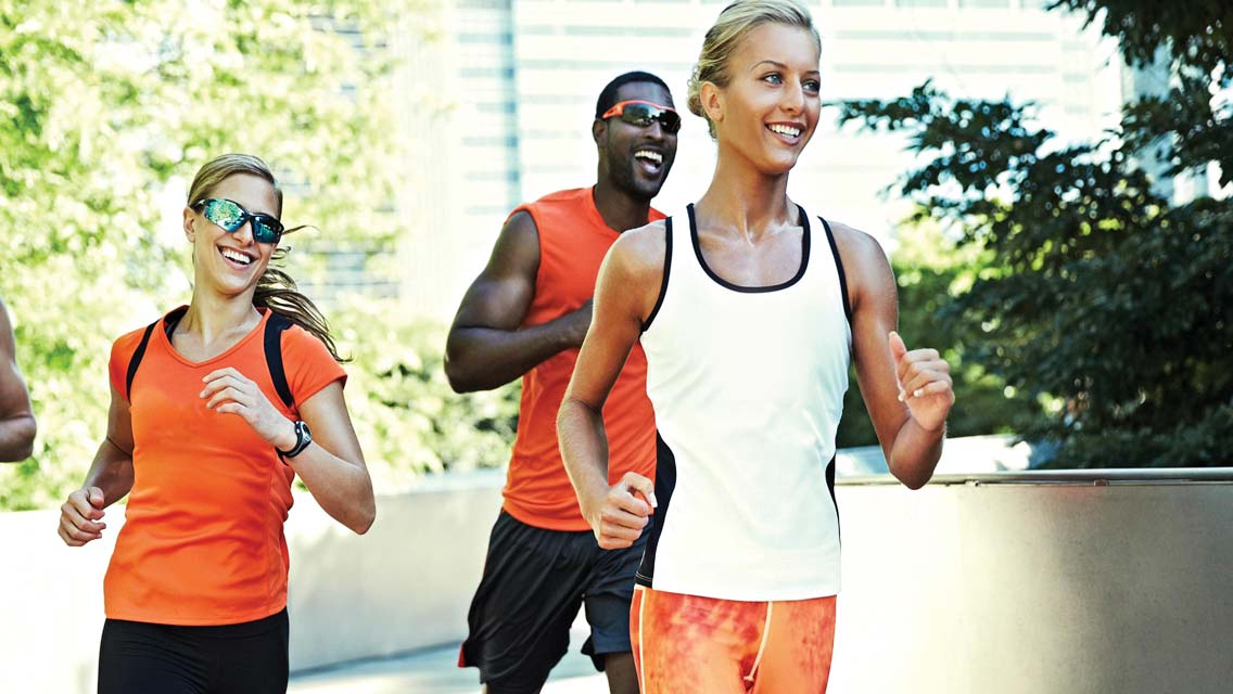 Three athletic adults jogging