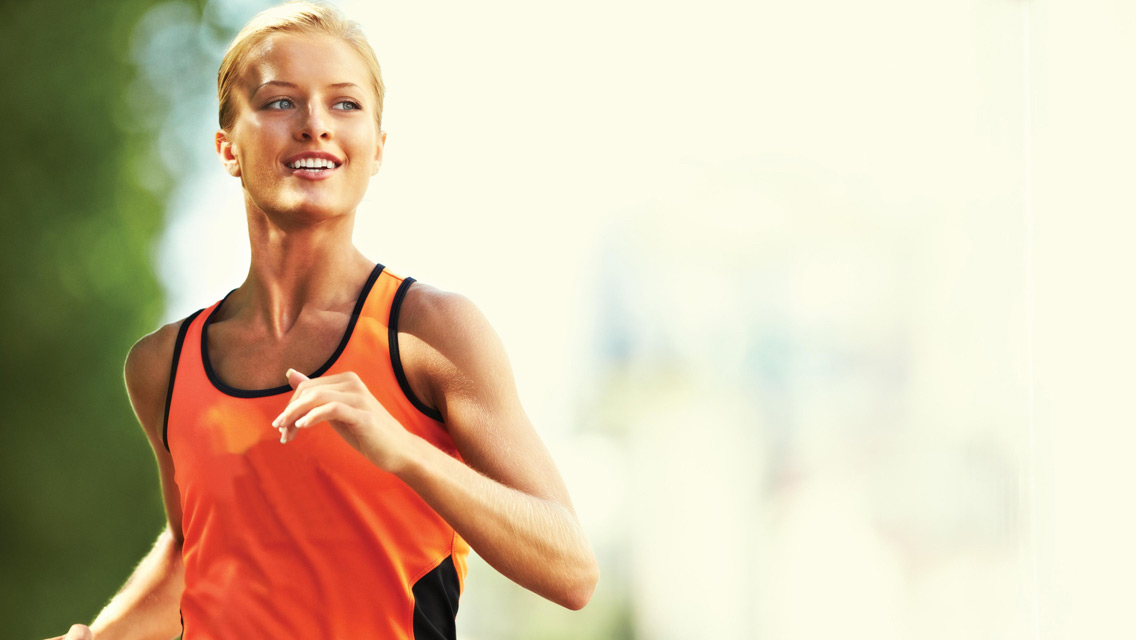 a young athletic woman running and smiling