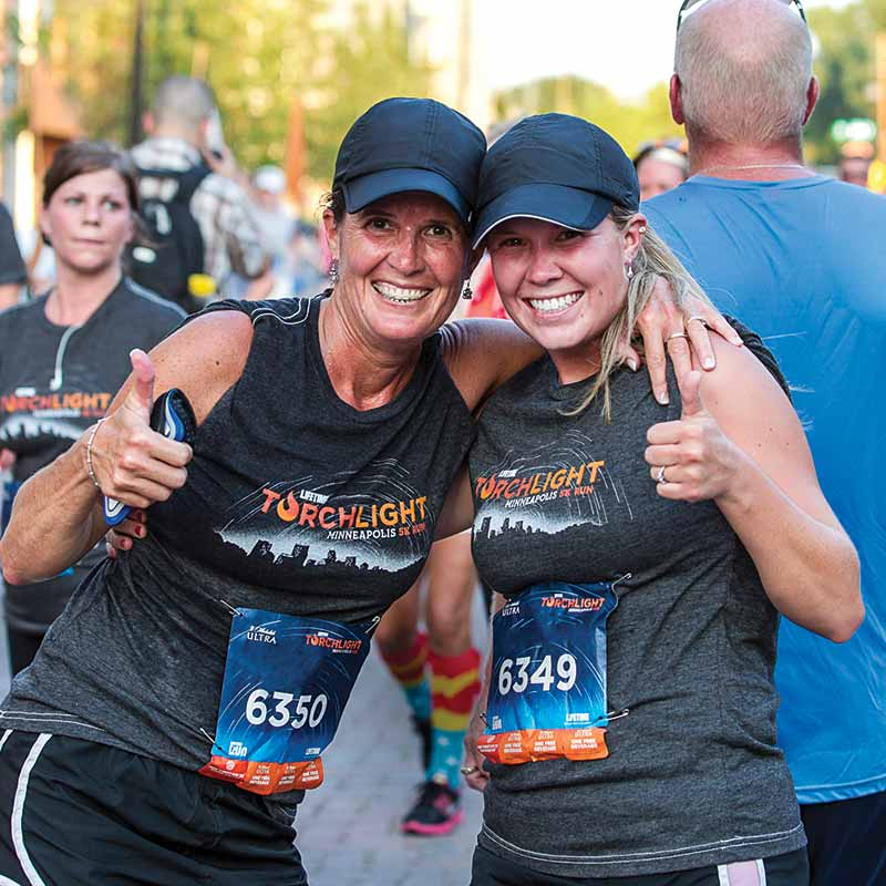 two women smiling after a marathon