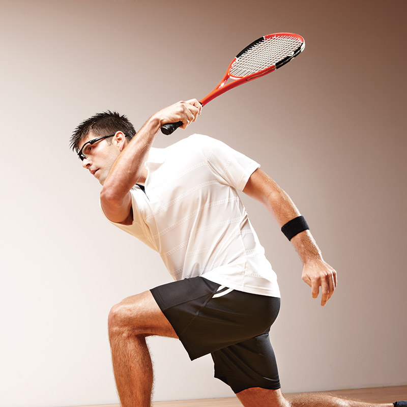 An atheltic man wearing squash gear and playing