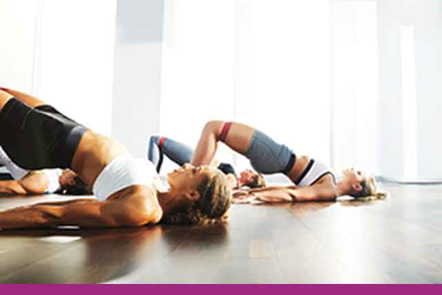 Three women and one man in a glute bridge position