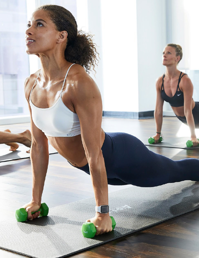 A woman in a fitness class with outstretched arms and an exultant smile