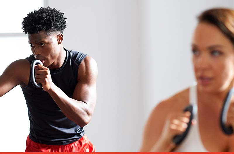 Two people practicing boxing moves in a group fitness class at Life Time