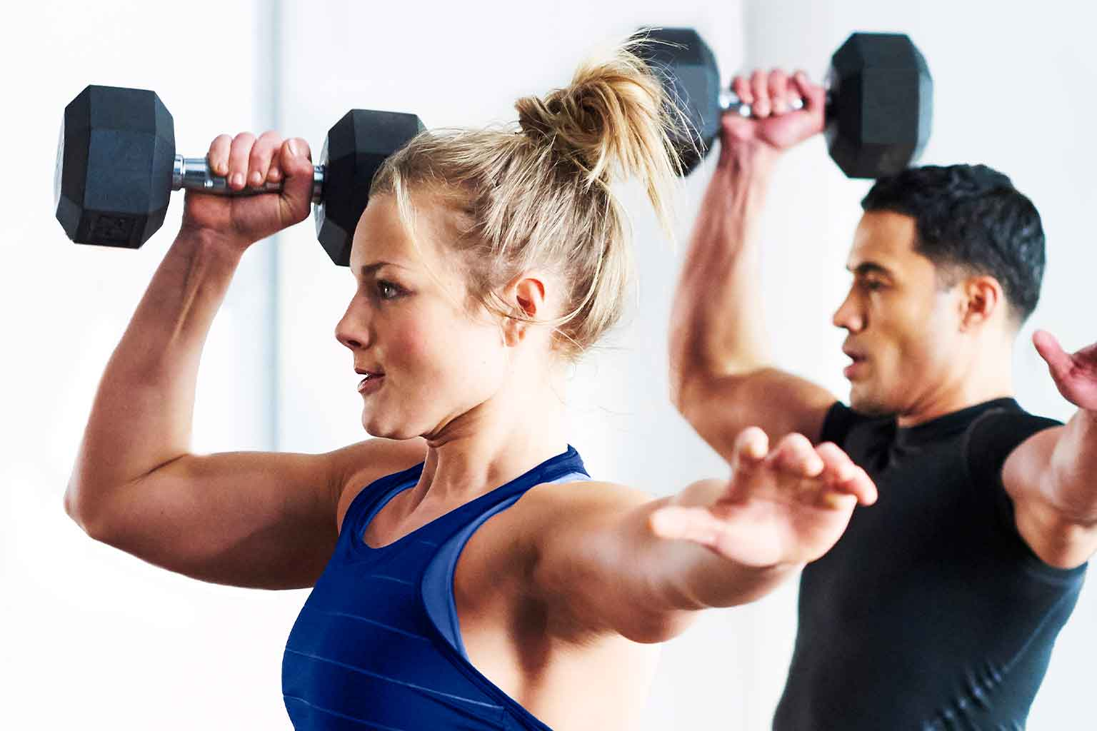A woman and a man in workout attire raising a dumbbell with the opposite hand reaching out for balance.