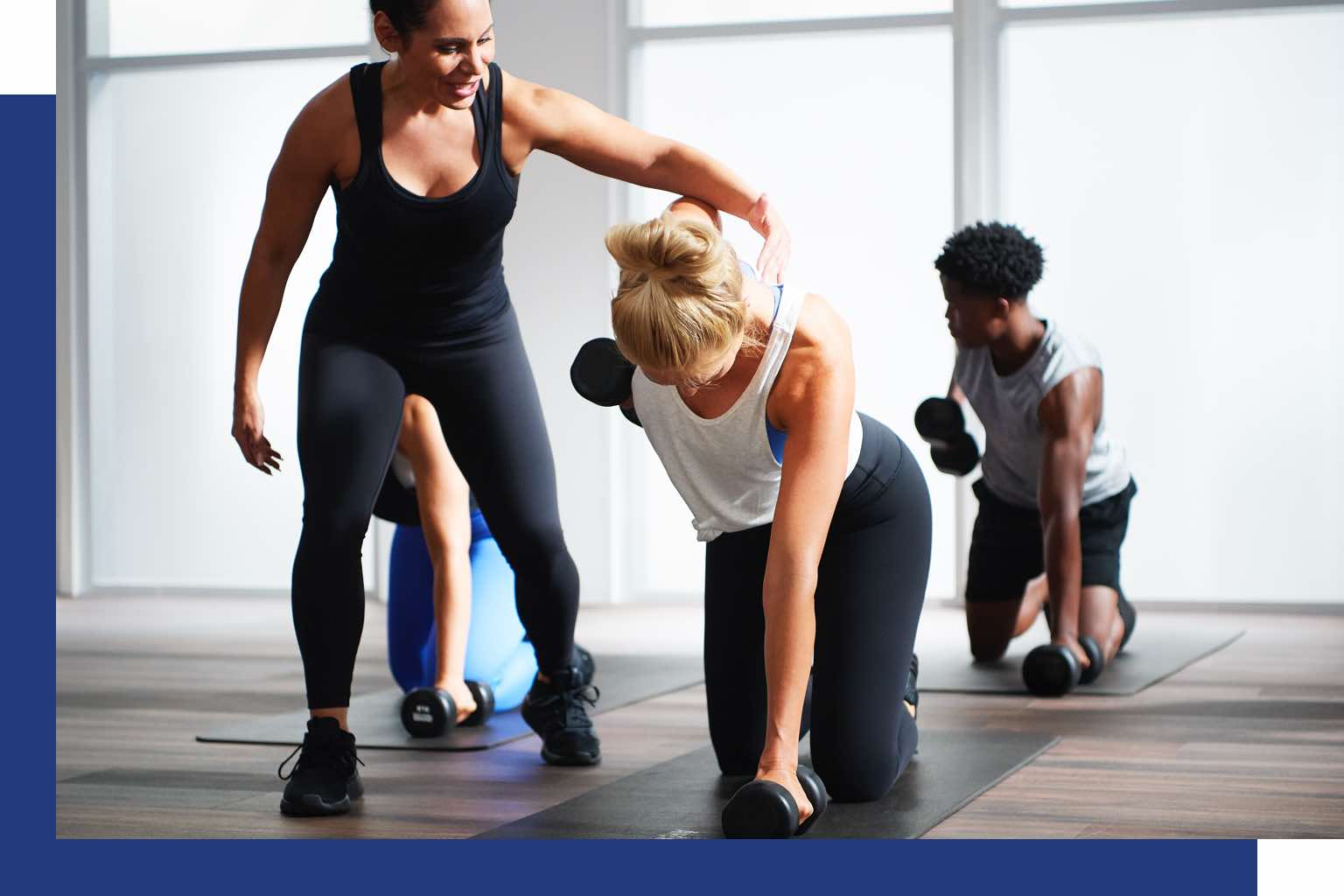 A woman doing a kneeling arm row with a teacher looking on and other participants in the background.
