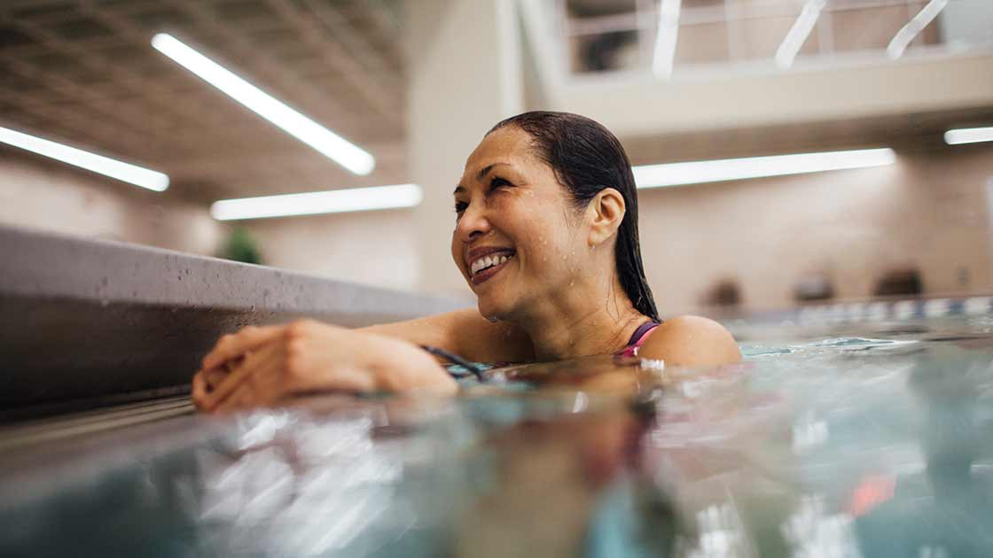 A woman in a pool at her adult swimming lesson